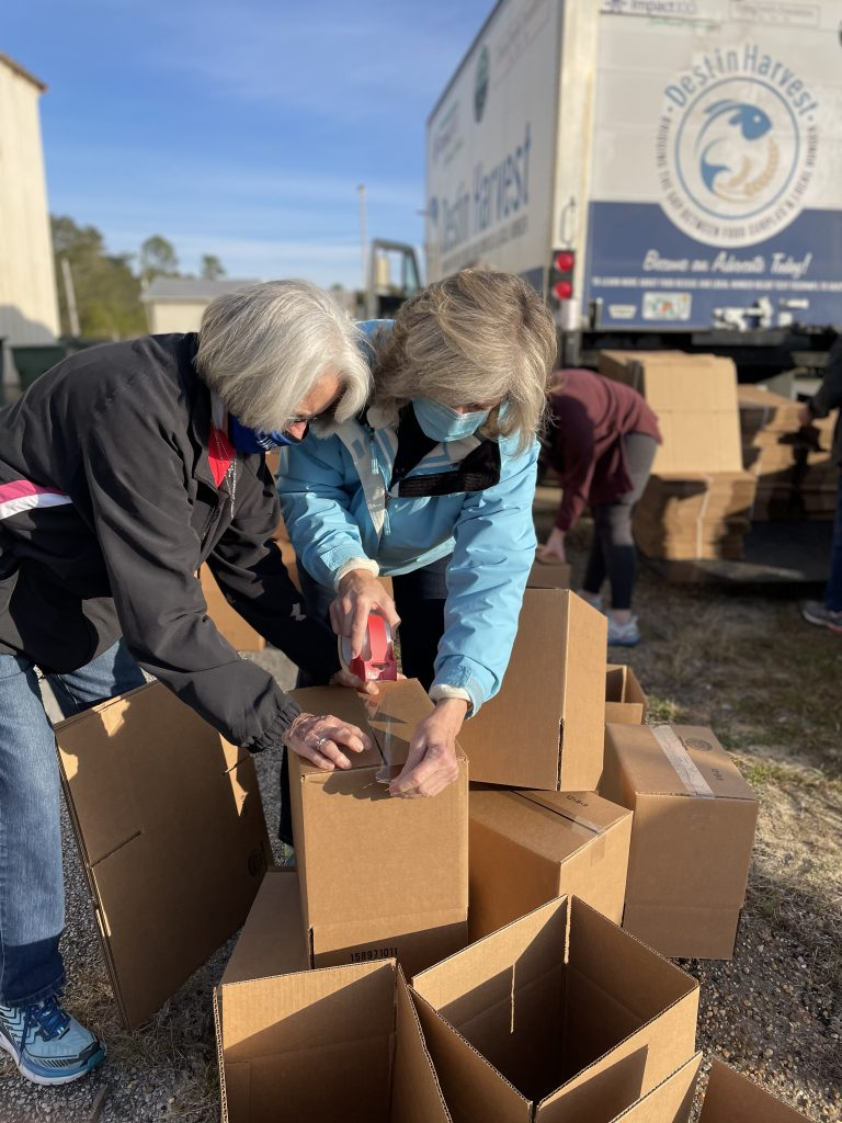 Two women preparing boxes at food distribution at NWFL Fairgrounds.